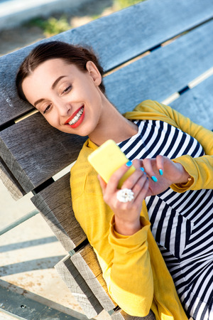 taking video: Woman in yellow having video call or taking selfie photo with yellow phone on wooden sunbed