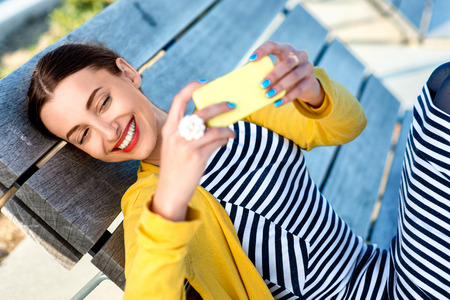 video call: Woman in yellow having video call or taking selfie photo with yellow phone on wooden sunbed