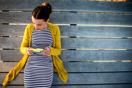 yellow dress: Young woman in yellow sweater using yellow phone on wooden sunbed, top view with space for your text