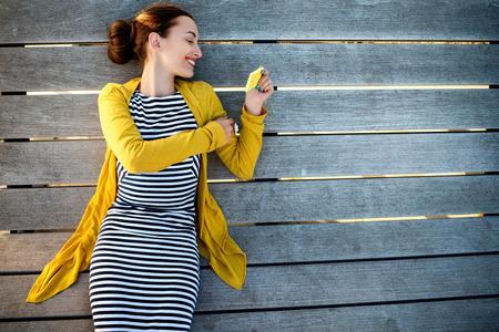 sueteres: Mujer joven en el suéter amarillo usando el teléfono amarillo en tumbona de madera, vista desde arriba con espacio para el texto
