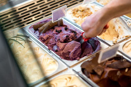 Picking ice cream from trays in the pastry shop Stock Photo