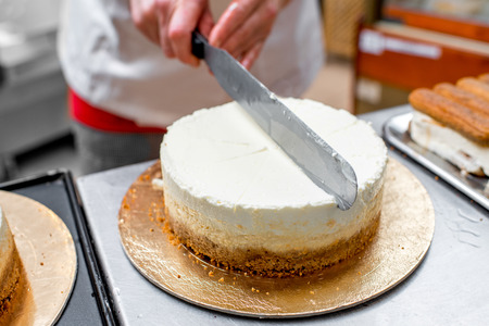 cheese cake: Woman smearing cream with knife on cheese cake