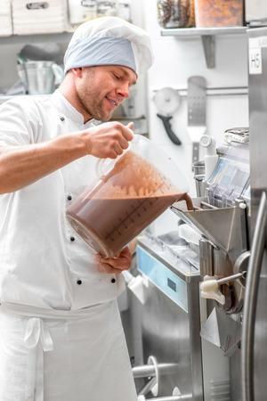 helado de chocolate: Confitero hermoso en el uniforme del cocinero producir helado con m�quina de helados Foto de archivo