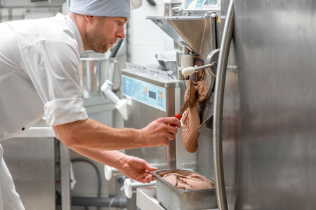 Handsome confectioner in chef uniform producing ice cream with ice cream machine