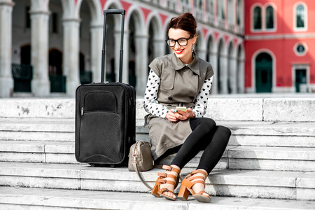 venecian: Young woman dressed in coat and glasses with travel bag sitting on the stairs at Republic square in Split city