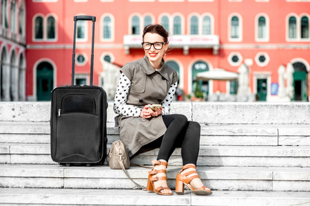 Young woman dressed in coat and glasses with travel bag sitting on the stairs at Republic square in Split city