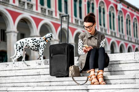 Jonge vrouw gekleed in jas en bril met reistas met behulp van de telefoon op de trap bij Republiek plein in Split stad