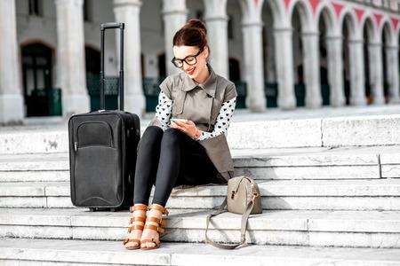 와 코트를 입고 젊은 여자는 분할 도시의 공화국 광장에서 계단에 전화를 사용하여 여행 가방과 안경 스톡 콘텐츠