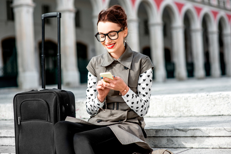 Young woman dressed in coat and glasses with travel bag using phone on the stairs at Republic square in Split city