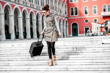bajando escaleras: Mujer joven caminando con bolsa de viaje por las escaleras en la Plaza de la Rep�blica en la ciudad de Split