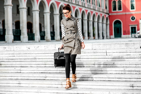 Young woman walking with travel bag down stairs at the Republic square in Split city