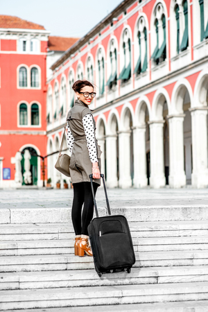 venecian: Young woman walking with travel bag up stairs at the Republic square in Split city Stock Photo