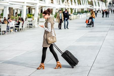 mujer con maleta: Mujer joven con la bolsa de viaje y el teléfono caminar en el paseo marítimo de Split cty en Croacia Foto de archivo