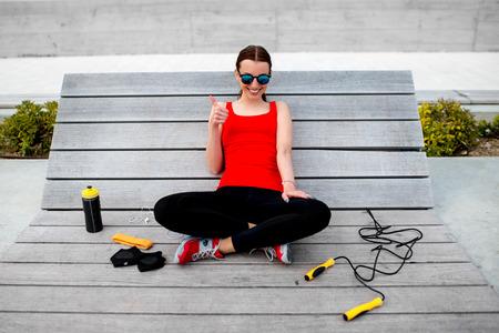 saltar la cuerda: Mujer joven del deporte con cuerda de saltar, tel�fono, guantes y botella acostada en la tumbona de madera Foto de archivo