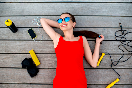 jump rope: Young sport woman with jump rope, phone, gloves and bottle lying on the wooden sunbed Stock Photo