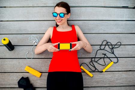 saltar la cuerda: Mujer joven del deporte con cuerda de saltar, guantes y una botella que muestra el tel�fono con pantalla en blanco acostado en la tumbona de madera