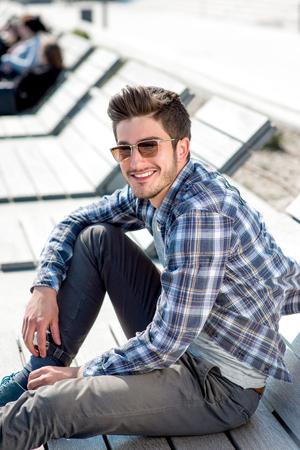 Junger stattlicher Mann in Freizeitkleidung mit Sonnenbrille auf dem Holzliegestuhl sitzen in der Stadt