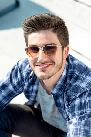 forelock: Young handsome man in casual clothes with sunglasses looking at camera