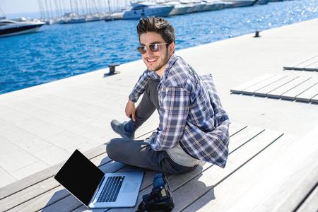 beau mec: Jeune photographe dans des v�tements d�contract�s assis avec un ordinateur portable et un appareil photo sur le transat pr�s de la mer avec des navires sur fond