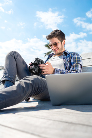 forelock: Young photographer holding camera while sitting with laptop on the sunbed in tropical city Stock Photo