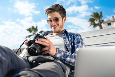 proffesional occupation: Young photographer holding camera while sitting with laptop on the sunbed in tropical city Stock Photo