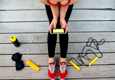 woman rope: Sporty woman holding phone with empty screen sitting on the sunbed with jump rope, gloves and drink bottle on background