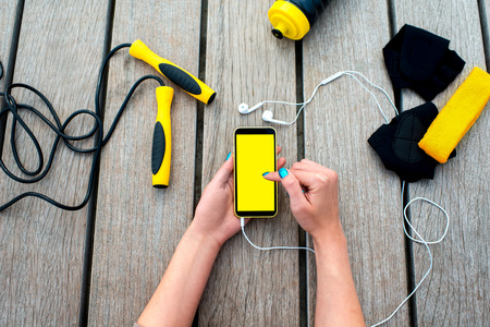sports equipment: Using mobile phone with empty screen on the wooden desk surrounded with sport equipment. Sport mobile application concept Stock Photo