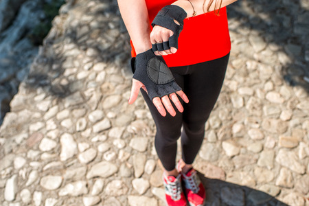 Woman putting on sports gloves in the park near the sea. Close up plan without face photo