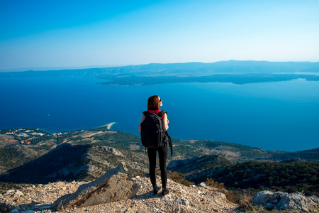 brac: Young woman traveler with backpack standing on the top of mountain. General back view Stock Photo