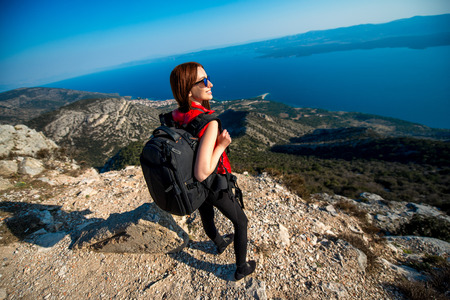 brac: Young woman traveler with backpack standing on the top of mountain