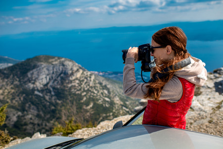 Young woman photographing landscapes near her car on the top of mountain