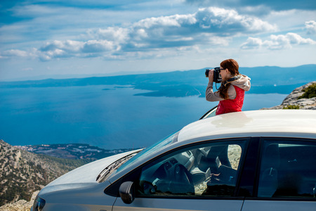 freedom nature: Young woman photographing landscapes near her car on the top of mountain