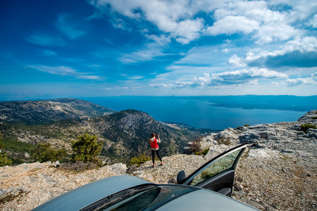 Young woman photographing landscapes near her car on the top of mountain photo