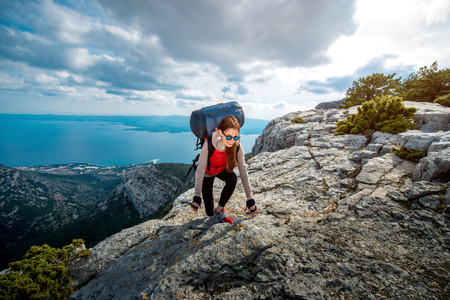 Young woman mountain climber with backpack and sleeping back hiking on the rocky mountain