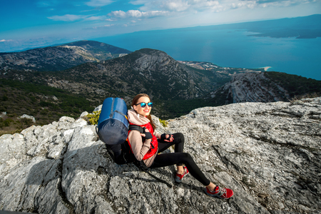 Young woman mountain climber with backpack and sleeping back resting on the rocky mountain photo