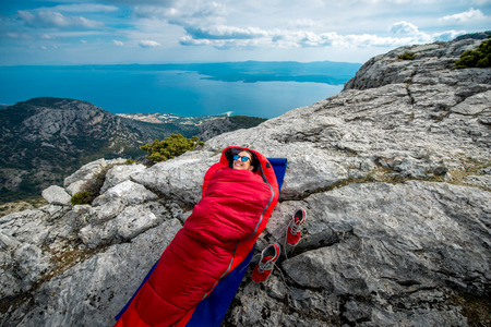 karemat: Young woman lying in red sleeping bag on the rocky mountain Stock Photo