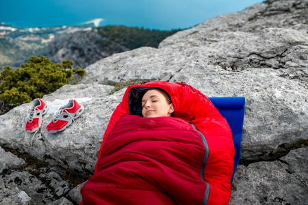 karemat: Young woman sleeping in red sleeping bag on the rocky mountain