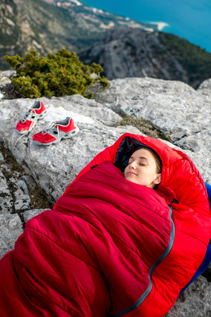 sleeping bag: Young woman sleeping in red sleeping bag on the rocky mountain