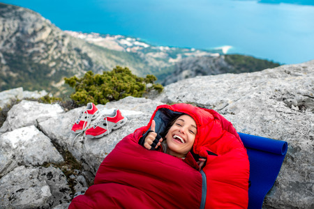 Young woman lying in red sleeping bag on the rocky mountain Stock Photo