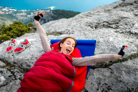 karemat: Young woman waking up in red sleeping bag on the rocky mountain Stock Photo