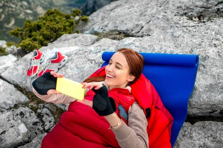 sleeping bag: Young woman taking selfie photo in red sleeping bag on the rocky mountain