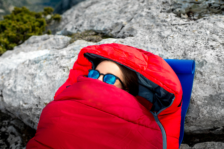 sleeping bag: Young woman lying in red sleeping bag on the rocky mountain Stock Photo