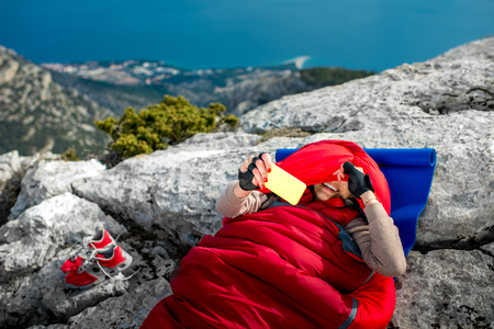karemat: Young woman taking selfie photo in red sleeping bag on the rocky mountain