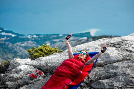 sleeping bag: Young woman waking up in red sleeping bag on the rocky mountain Stock Photo