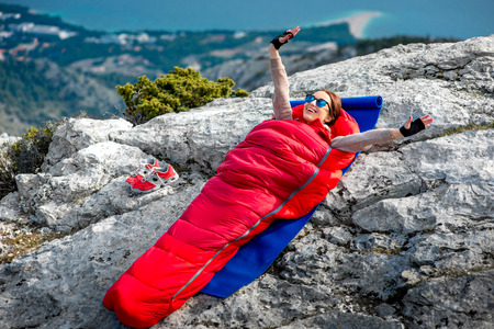 Young woman waking up in red sleeping bag on the rocky mountain Stock Photo