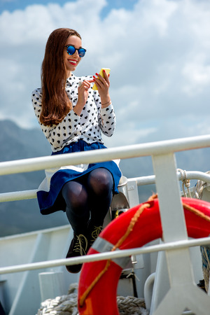 Young woman dressed in shirt and skirt sailing on cruise liner or ferry with sea and mountain background