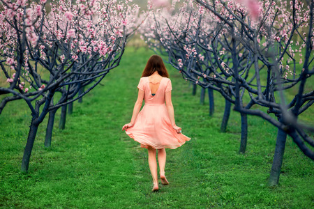 Young woman enjoying spring in the green field with blooming trees