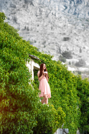 pink dress: Beautiful woman in pink dress standing with coffee cup on the balcony of green house in the mountains Stock Photo