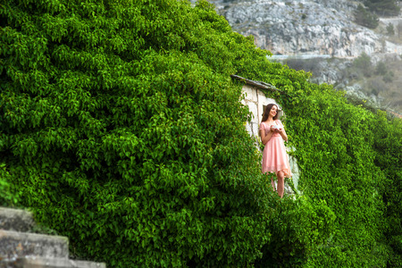 young female: Beautiful woman in pink dress standing with coffee cup on the balcony of green house in the mountains Stock Photo