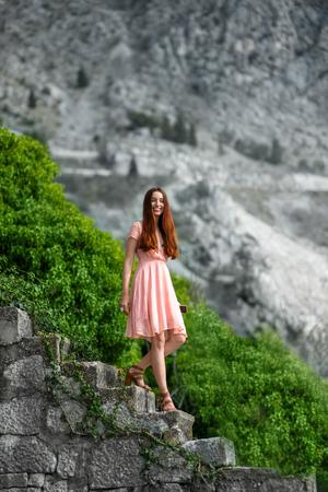 going down: Mujer joven en vestido rosa bajando escaleras con la naturaleza de fondo preciosa en la ciudad vieja